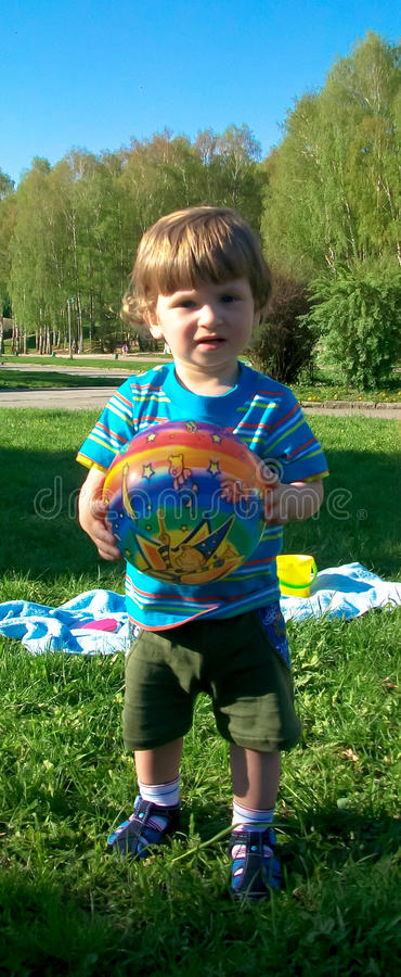 Chłopiec bawić się piłkę na trawie zdjęcia royalty free