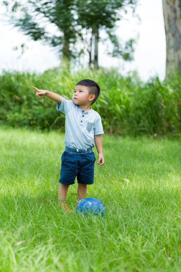 Chłopiec bawić się piłkę nożną przy plenerowym obraz royalty free