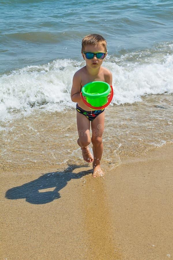 Chłopiec bawić się przy morzem z wiadrem Chłopiec ma plażową zabawę zdjęcia stock