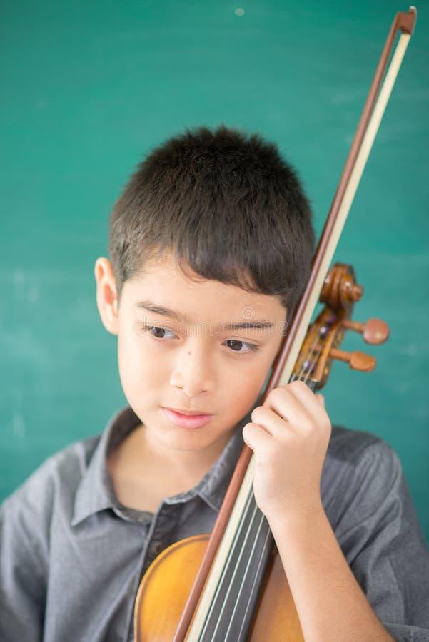 Chłopiec bawić się skrzypce w muzycznej klasie i ćwiczą obrazy royalty free