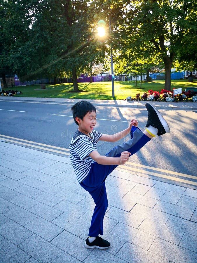 Chłopiec bawić się tae kwon robi pod światłem słonecznym zdjęcie royalty free