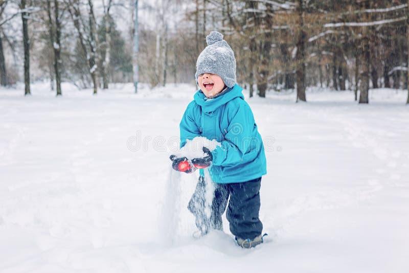 Chłopiec bawić się w śniegu outside w zimie obrazy stock