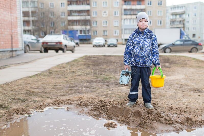 Chłopiec bawić się w błotnistej kałuży obraz stock