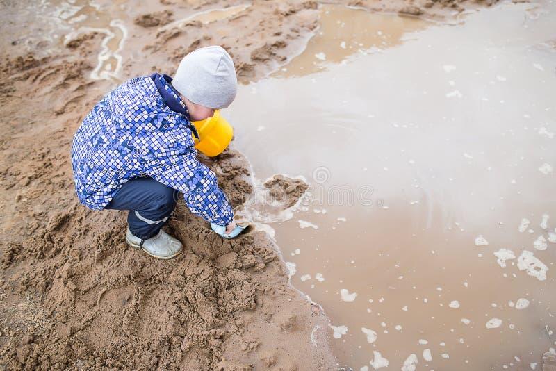 Chłopiec bawić się w błotnistej kałuży obraz royalty free