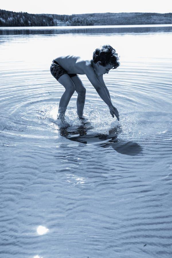 Chłopiec bawić się w wodzie obraz stock