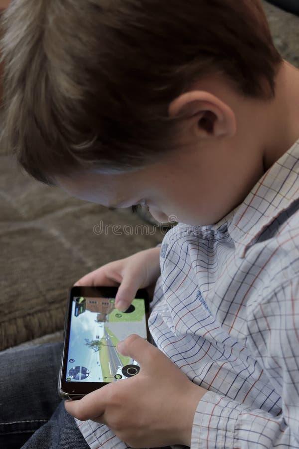 Chłopiec bawić się wideo grę na telefonie komórkowym obraz royalty free