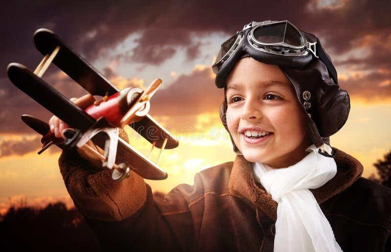 Chłopiec bawić się z drewnianym zabawkarskim samolotem zdjęcia royalty free