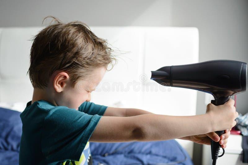 Chłopiec bawić się z elektryczną włosianą suszarką zdjęcie stock