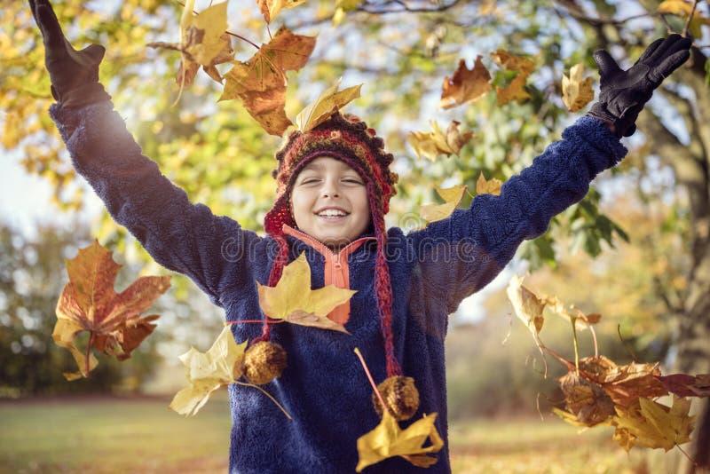 Chłopiec bawić się z jesień liśćmi w parku fotografia stock