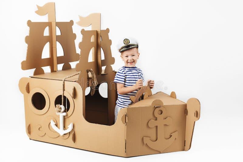 Chłopiec bawić się z kartonowym statkiem na białym tle Happ fotografia stock