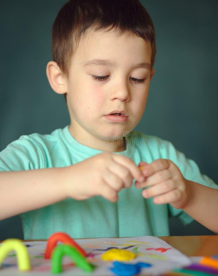 Chłopiec bawić się z kolor sztuki ciastem obrazy royalty free