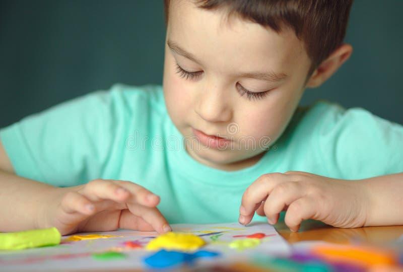 Chłopiec bawić się z kolor sztuki ciastem zdjęcia royalty free