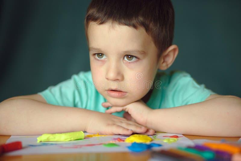 Chłopiec bawić się z kolor sztuki ciastem obraz stock