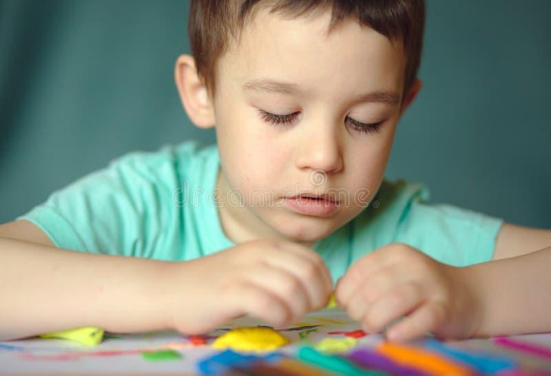 Chłopiec bawić się z kolor sztuki ciastem zdjęcie stock