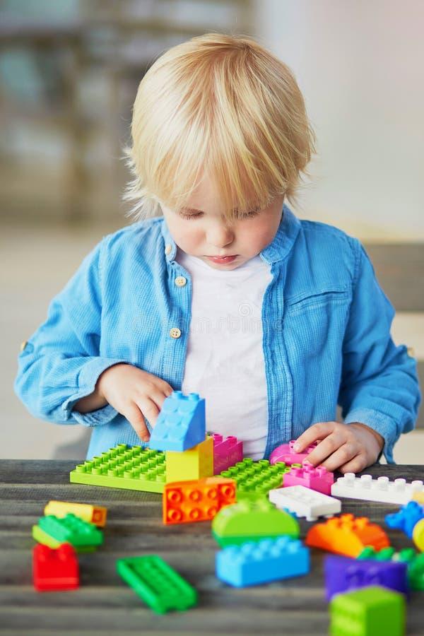 Chłopiec bawić się z kolorowymi plastikowymi budowa blokami zdjęcie royalty free