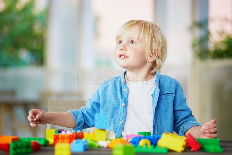 Chłopiec bawić się z kolorowymi plastikowymi budowa blokami zdjęcia royalty free