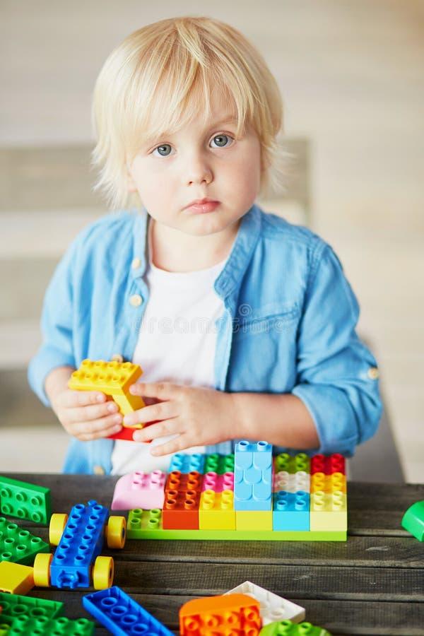 Chłopiec bawić się z kolorowymi plastikowymi budowa blokami obrazy royalty free