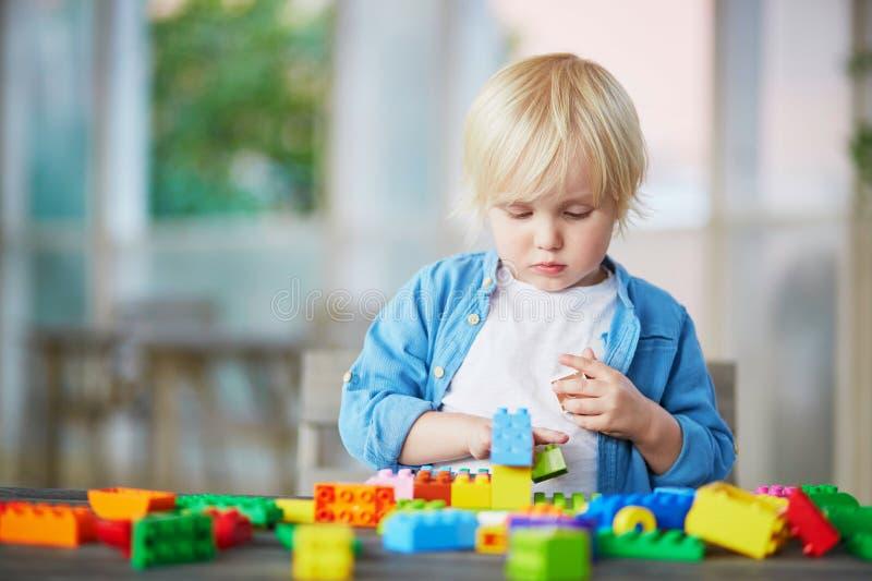 Chłopiec bawić się z kolorowymi plastikowymi budowa blokami zdjęcia stock
