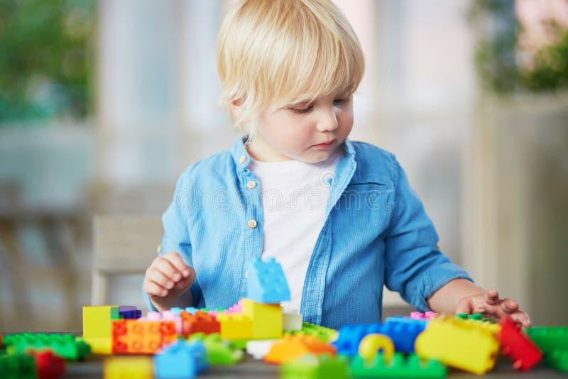 Chłopiec bawić się z kolorowymi plastikowymi budowa blokami fotografia royalty free
