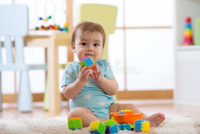 Chłopiec bawić się z kolorowymi plastikowymi cegłami na podłodze Berbeć ma zabawę i buduje z konstruktor cegieł obrazy stock