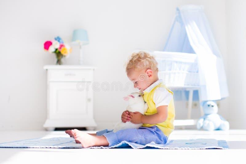 Chłopiec bawić się z królika zwierzęciem domowym zdjęcia stock