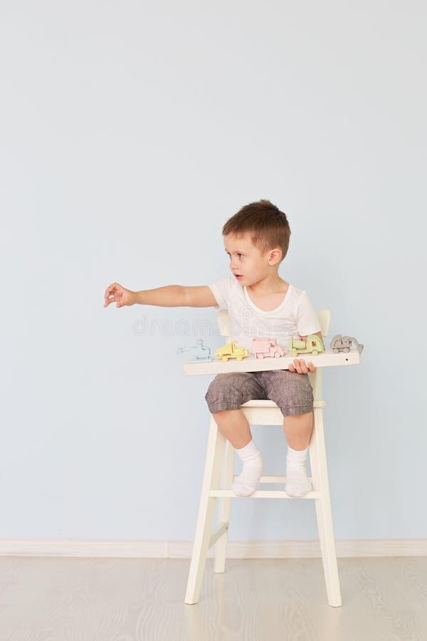 Chłopiec bawić się z maszyną i siedzi na krześle zdjęcie royalty free
