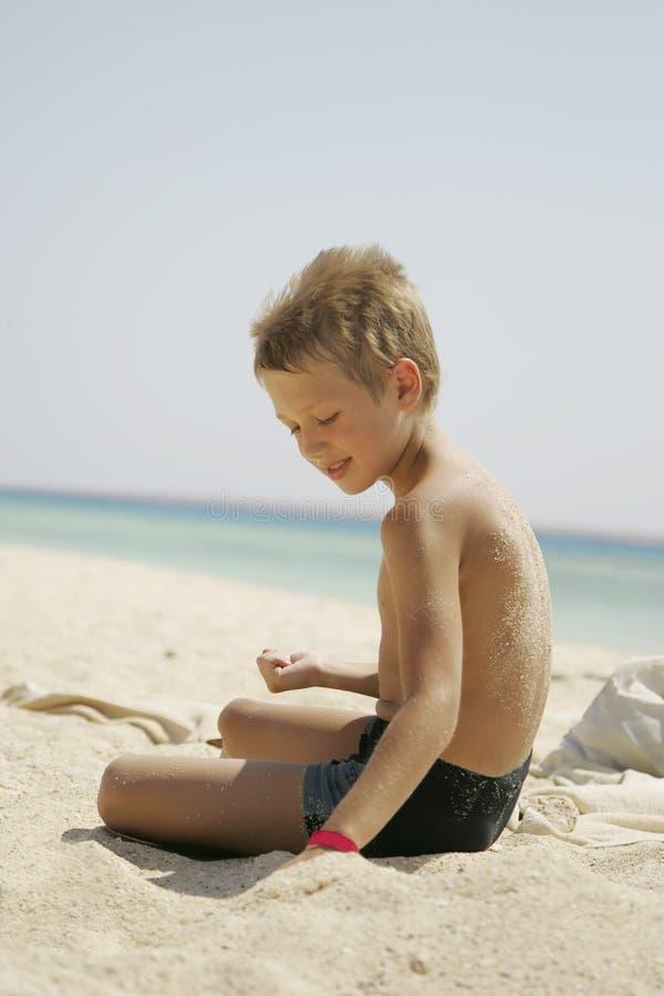 Chłopiec bawić się z piaskiem przy morzem zdjęcia stock