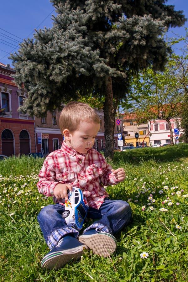 Chłopiec bawić się z trawy i zabawki samochodem policyjnym w naturze obrazy royalty free
