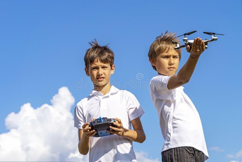 Chłopiec bawić się z trutniem w letnim dniu outdoors przeciw niebieskiemu niebu zdjęcia stock