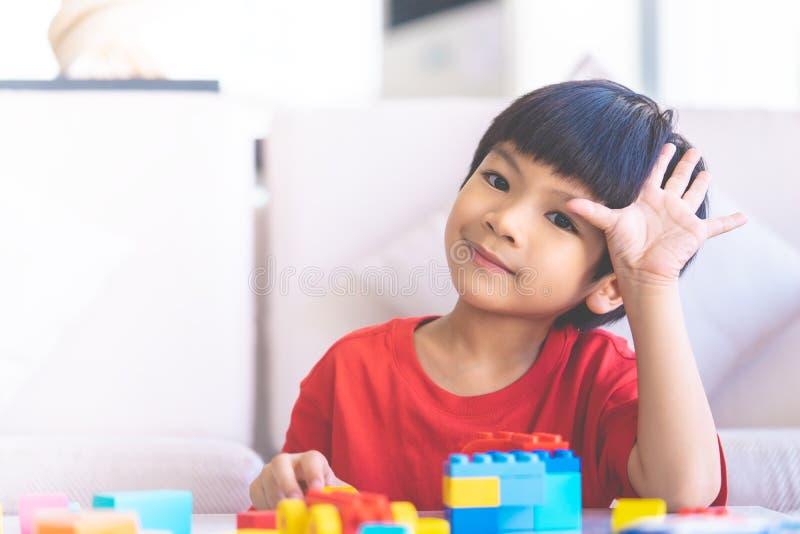 Chłopiec bawić się zabawka bloki w żywej izbowej ręce w górę mówi cześć obrazy stock