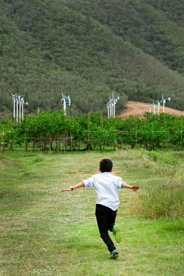 Chłopiec bieg w polu i silnikach wiatrowych w backgroun fotografia stock