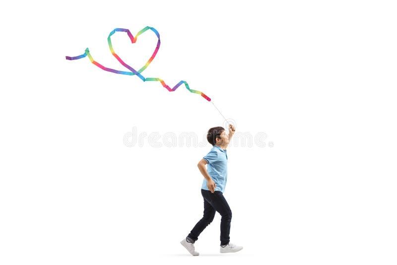Chłopiec bieg z rytmicznym faborkiem i robić kierowemu kształtowi obrazy royalty free