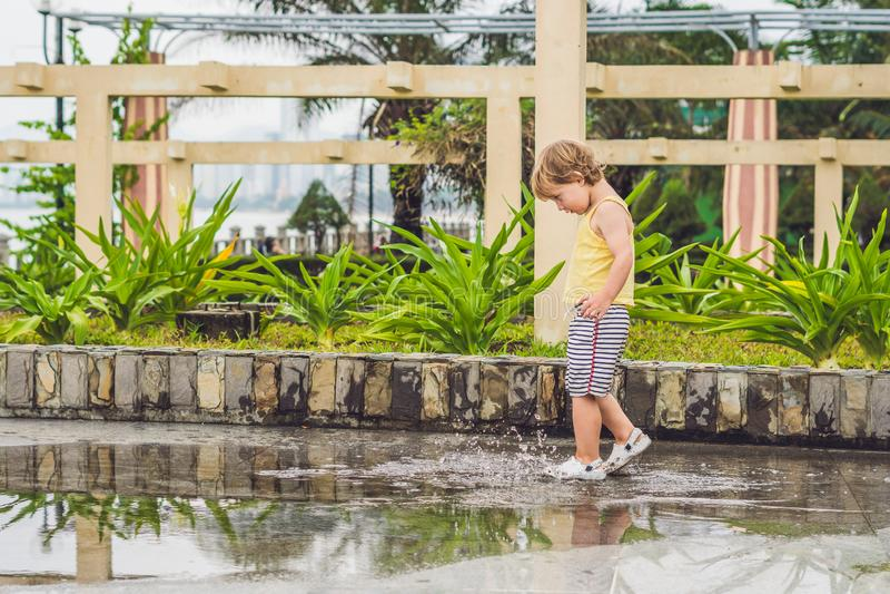 Chłopiec biega przez kałuży Lato plenerowy obraz stock