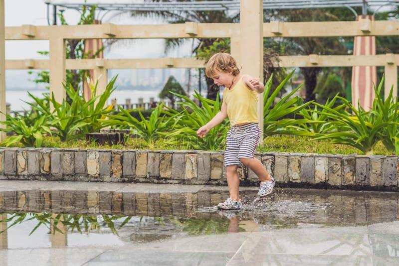 Chłopiec biega przez kałuży Lato plenerowy zdjęcia royalty free