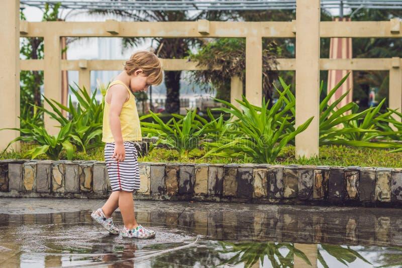 Chłopiec biega przez kałuży Lato plenerowy fotografia royalty free