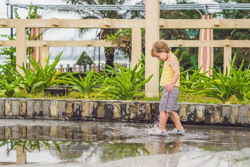 Chłopiec biega przez kałuży Lato plenerowy obrazy royalty free