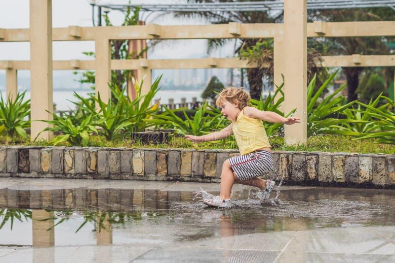 Chłopiec biega przez kałuży Lato plenerowy obrazy stock