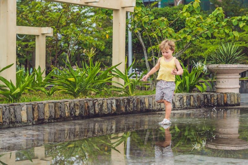 Chłopiec biega przez kałuży Lato plenerowy zdjęcia stock