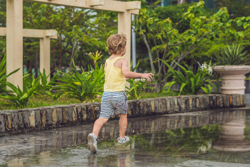 Chłopiec biega przez kałuży Lato plenerowy obraz royalty free