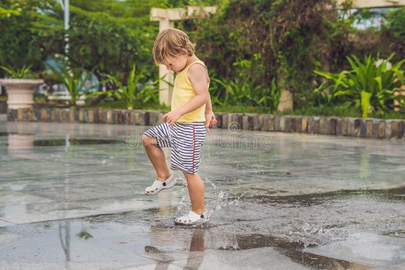 Chłopiec biega przez kałuży Lato plenerowy zdjęcie stock