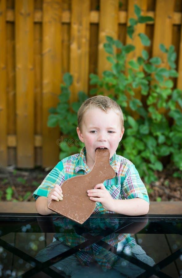 Chłopiec Bierze kąsek Z Czekoladowego królika fotografia stock