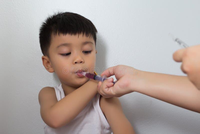 Chłopiec bierze lekarstwo od strzykawki obraz stock