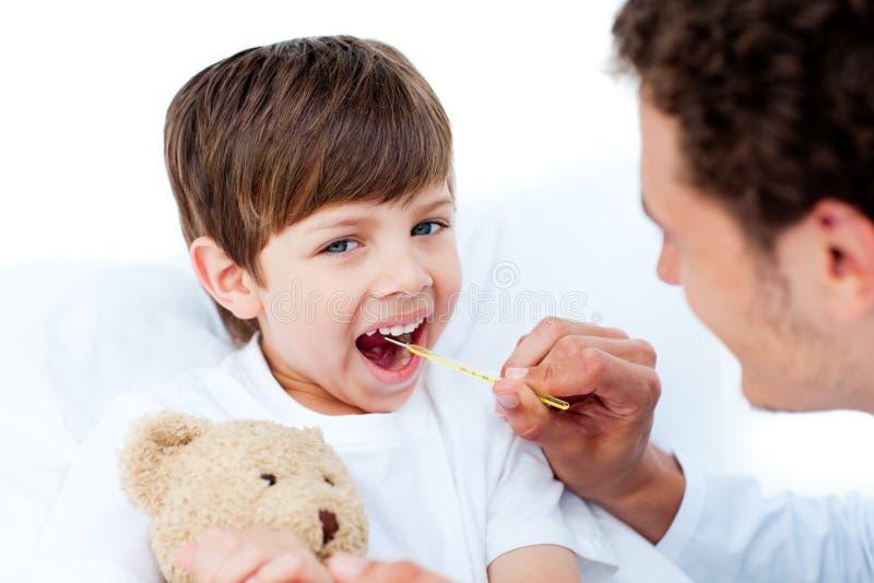 chłopiec bierze temperaturowych potomstwa doktorski mały s obrazy stock