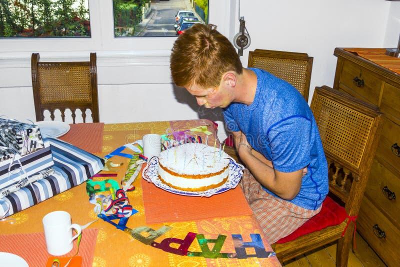 Chłopiec blowes out świeczki przy urodzinowym tortem obraz royalty free