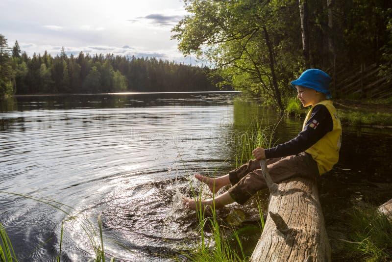 Chłopiec bryzga jego ciekami w jeziorze zdjęcia royalty free