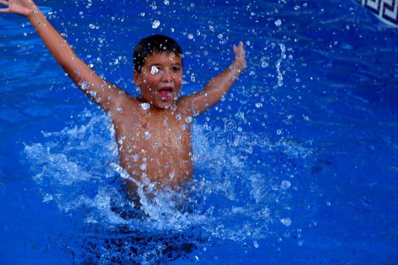Chłopiec bryzga w pływackim basenie obrazy royalty free