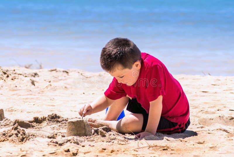 Chłopiec buduje piaska kasztel na plaży obraz stock