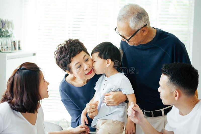 Chłopiec całowania babcia na policzkach z całą Azjatycką rodziną zdjęcia royalty free