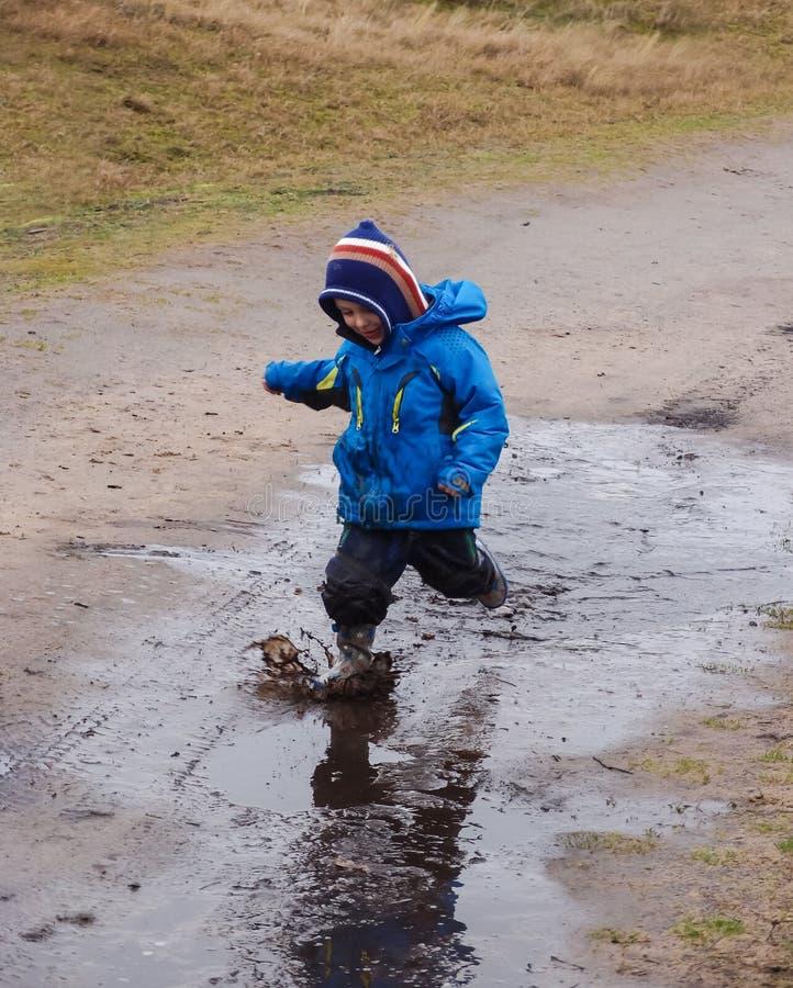Chłopiec chełbotanie w błotnistej kałuży obraz royalty free