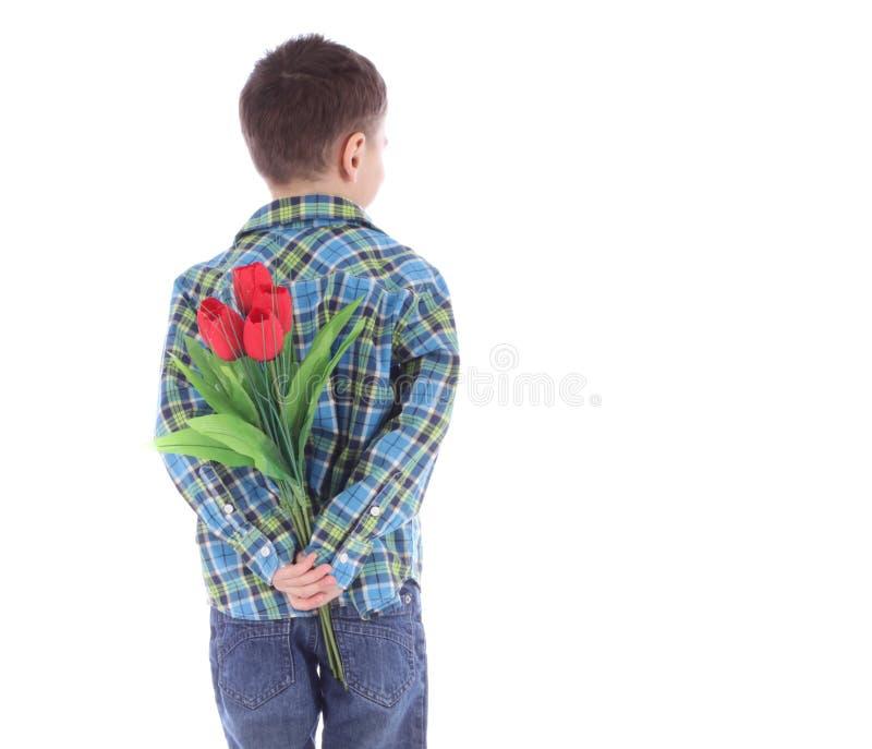 Chłopiec chuje kwiaty czerwoni tulipany za ja obrazy stock